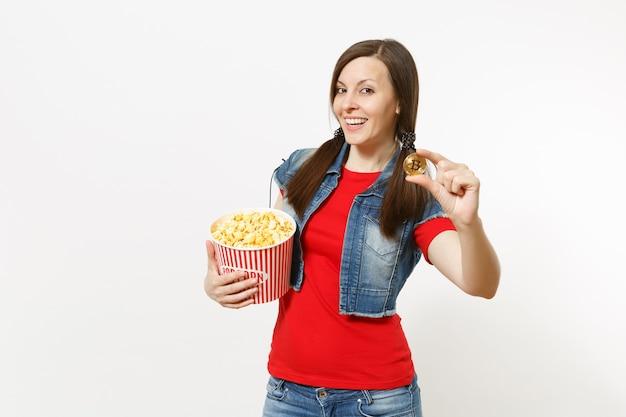 흰색 배경에 격리된 팝콘과 비트코인 양동이를 들고 영화 영화를 보고 있는 캐주얼한 옷을 입고 웃고 있는 매력적인 브루네트 여성의 초상화. 영화 개념의 감정.