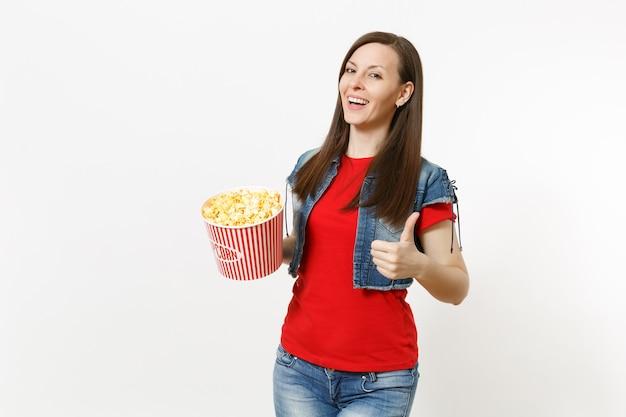 캐주얼 옷을 입고 영화 영화를 보고, 팝콘 양동이를 들고 흰색 배경에 격리된 엄지손가락을 보여주는 젊은 웃고 있는 매력적인 브루네트 여성의 초상화. 영화 개념의 감정.