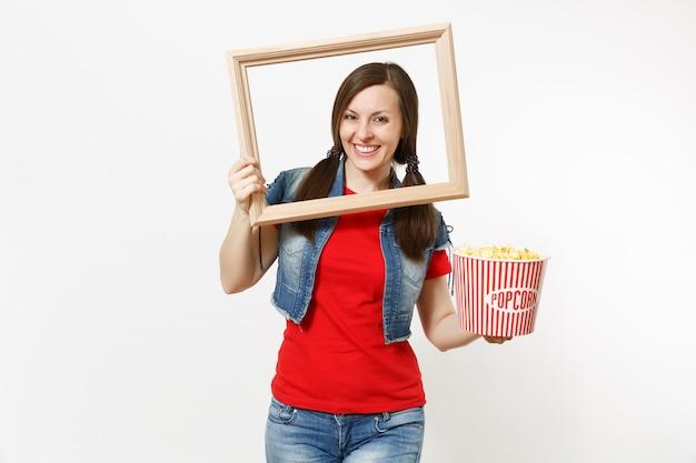 흰색 배경에 격리된 팝콘 양동이와 나무 액자를 들고 영화 영화를 보고 있는 캐주얼한 옷을 입고 웃고 있는 매력적인 브루네트 여성의 초상화. 영화 개념의 감정.