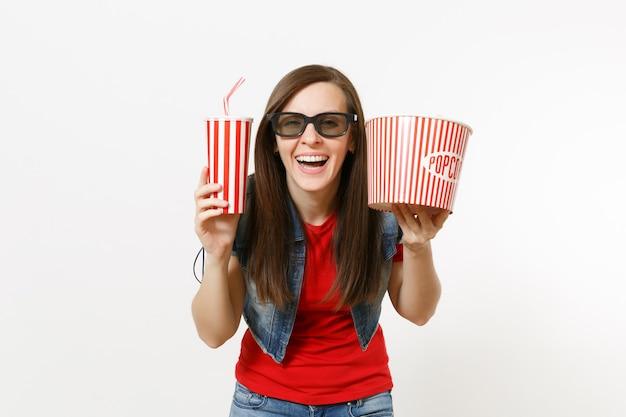 흰색 배경에 격리된 팝콘 양동이와 플라스틱 컵의 소다 또는 콜라를 들고 영화를 보고 있는 3d 아이맥스 안경을 쓴 젊고 매력적인 여성의 초상화. 영화 개념의 감정.