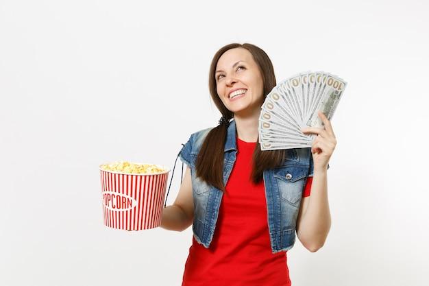 캐주얼 옷을 입고 영화를 보고 웃고 있는 젊은 여성의 초상화, 팝콘 양동이와 달러 묶음, 흰색 배경에 격리된 현금 돈을 들고 있습니다. 영화 개념의 감정.