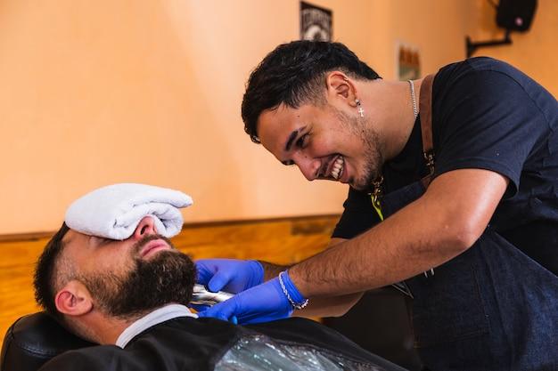 流行に敏感なひげを生やして若い笑顔の床屋の肖像画