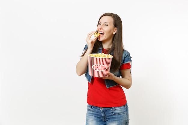 캐주얼 옷을 입고 영화를 보고, 팝콘 양동이를 들고, 먹고, 흰색 배경에 격리된 enjoing을 입고 웃고 있는 젊고 아름다운 브루네트 여성의 초상화. 영화 개념의 감정.