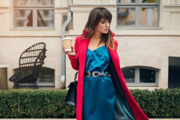 Портрет молодой улыбающейся красивой стильной женщины, идущей по улице города в красном халате, пить кофе