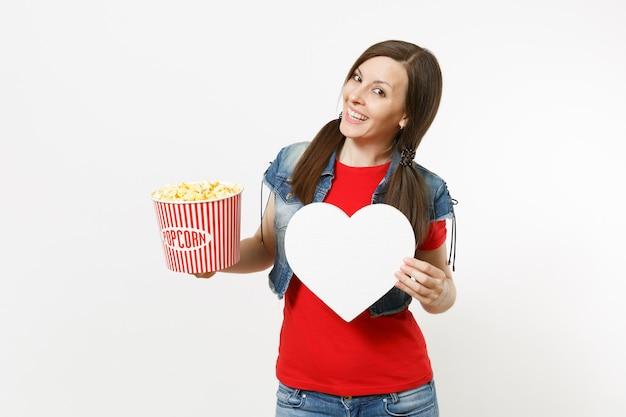 흰색 배경에 격리된 복사 공간이 있는 팝콘과 흰색 하트 양동이를 들고 영화 영화를 보고 있는 캐주얼한 옷을 입고 웃고 있는 젊고 아름다운 여성의 초상화. 영화 개념의 감정.