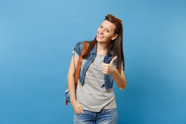 Портрет молодого усмехаясь красивого студента женщины в джинсовой одежде с рюкзаком, оранжевыми сердечными очками показывая большой палец руки вверх изолированный на голубой предпосылке. обучение в колледже. скопируйте место для рекламы.