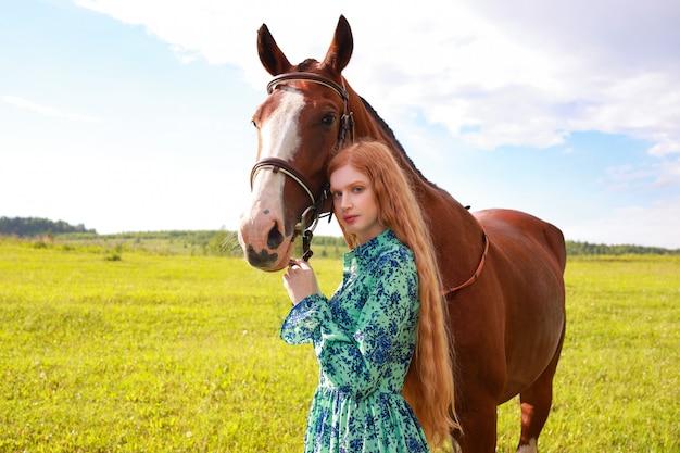 茶色の馬を屋外で歩く若い笑顔の美しい女性の肖像画