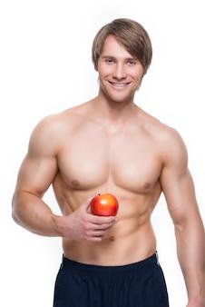 Портрет молодого улыбающегося культуриста, держащего яблоко в руке