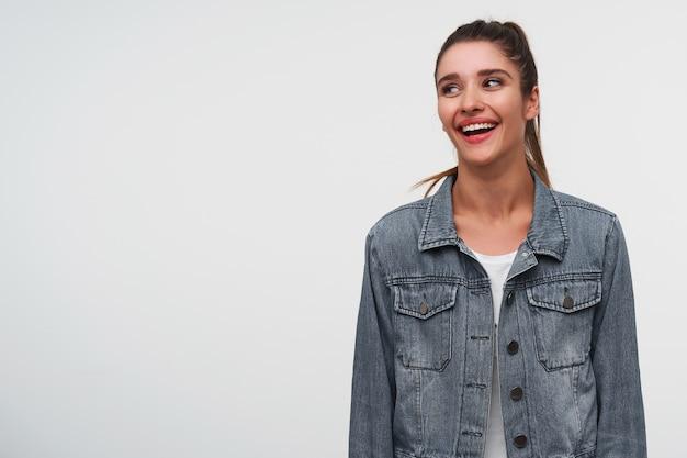 若い笑顔のブルネットの女性の肖像画は、白いtシャツとデニムのジャケットを着て、幸せな表情で目をそらし、左側にコピースペースと白い背景の上に立っています。
