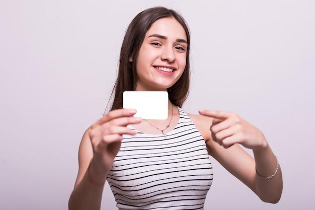 Портрет молодой улыбающейся деловой женщины в бежевом платье, держащей пустую кредитную карту на сером фоне