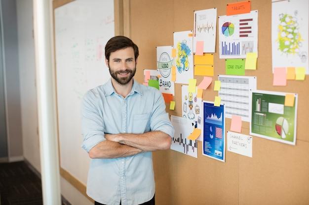 Портрет молодого улыбающегося бизнесмена с руками, пересеченными мягкой доской в офисе