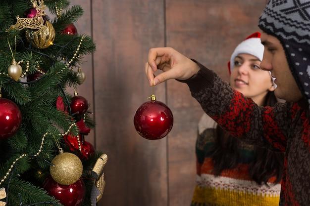 웃긴 모자를 쓰고 웃고 있는 젊은 부부의 초상화, 거실에 있는 큰 크리스마스 트리에 장식과 장식품을 걸어 크리스마스 장식