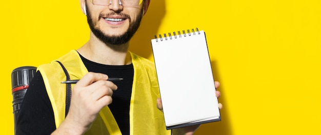 빈 노트북에 펜으로 보여주는 젊은 웃는 엔지니어 남자의 초상화