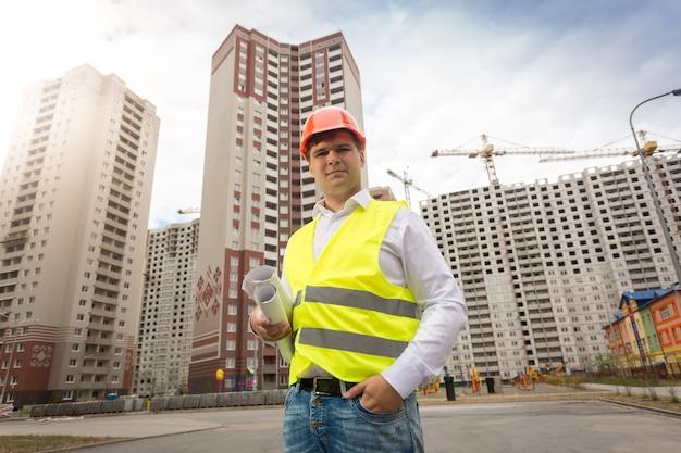 Портрет молодого улыбающегося инженера, стоящего на строительной площадке