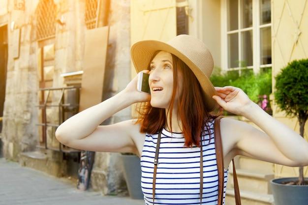 스마트폰으로 서 있는 젊은 웃는 패션 소녀의 초상화