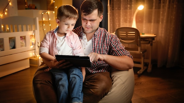 인터넷을 검색하고 밤에 침실에서 어린 아들과 함께 만화를 보고 있는 웃고 있는 젊은 아버지의 초상화. 아동 교육과 가족이 밤에 함께 시간을 보내는 개념.