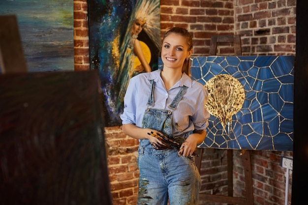 アートブラシを保持しているアートスタジオの画家の彼女のアートワークと若い笑顔の女性アーティストの肖像画...
