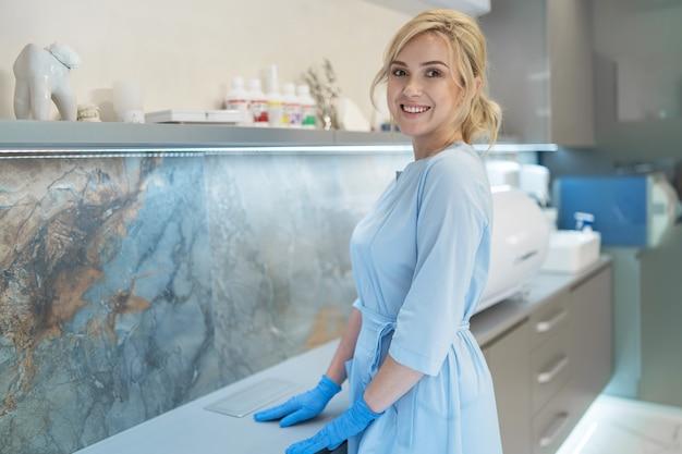 Портрет молодой улыбающейся женщины-стоматолога в современном стоматологическом кабинете