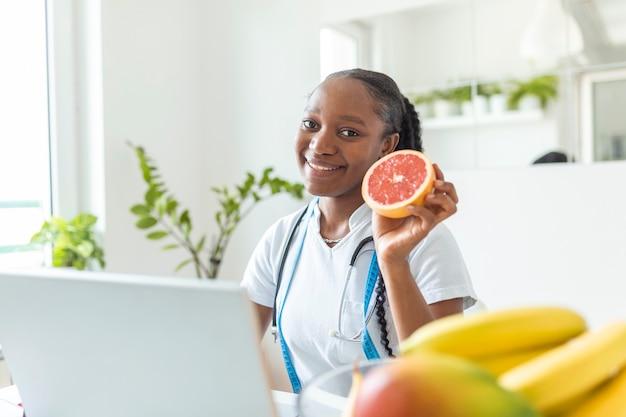 診察室で若い笑顔の女性栄養士の肖像画。健康的な果物、ジュース、巻尺を備えた栄養士用デスク。ダイエット計画に取り組んでいる栄養士。