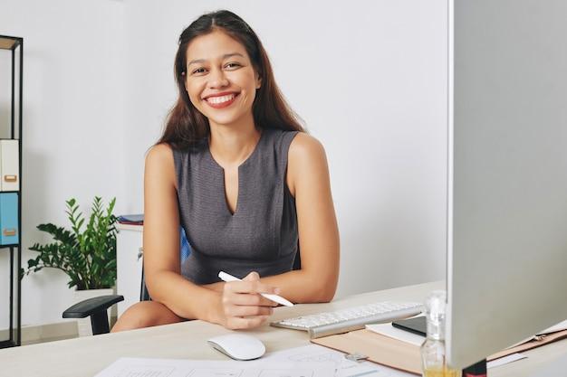 彼女の机でコンピューターと新しいモバイルアプリケーションのスケッチプロジェクトに取り組んでいる若い笑顔の女性uiデザイナーの肖像画