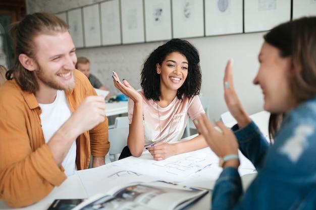 Портрет молодой улыбающейся группы людей, работающих вместе в офисе
