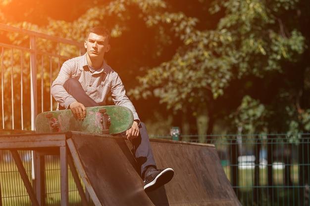 晴れた夏の日にスケートパークでスケートボードに座ってスタイリッシュなシャツのスニーカーとズボンに身を包んだ若い笑顔の男の肖像画