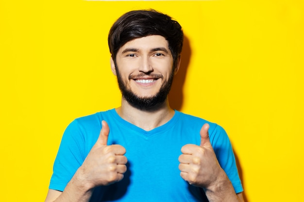 엄지 손가락을 보여주는 파란색 셔츠에 젊은 웃는 남자의 초상화