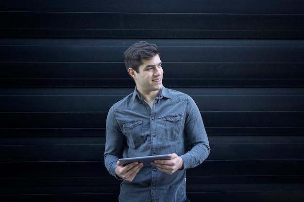 タブレットコンピューターを保持し、脇を見て若い笑顔のハンサムな男の肖像画