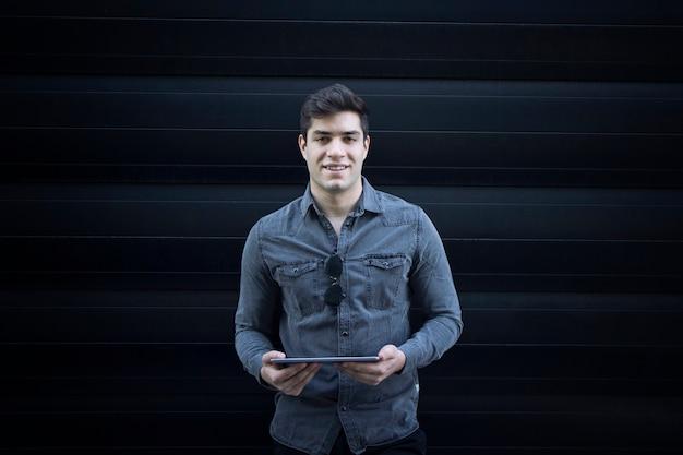 タブレットコンピューターを保持し、正面をまっすぐ見ている若い笑顔のハンサムな男の肖像画