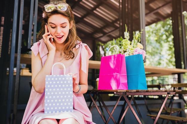 Портрет молодой улыбающейся счастливой привлекательной женщины, сидящей в кафе, разговаривающей по телефону с сумками, летней модной одежды, розового хлопкового платья, удивленного лица