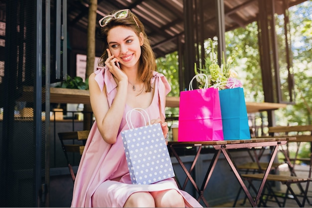 Портрет молодой улыбающейся счастливой привлекательной женщины, сидящей в кафе, разговаривающей по телефону с сумками, летней модной одежды, розового хлопкового платья, модной одежды