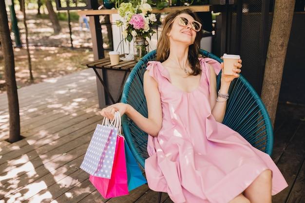 Портрет молодой улыбающейся счастливой привлекательной женщины, сидящей в кафе с хозяйственными сумками, пьющими кофе, летним модным нарядом, хипстерским стилем, розовым хлопковым платьем, модной одеждой
