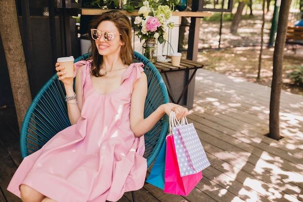 Портрет молодой улыбающейся счастливой привлекательной женщины, сидящей в кафе с хозяйственными сумками, пить кофе