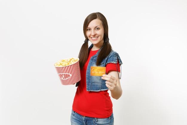 흰색 배경에 격리된 팝콘과 신용카드 양동이를 들고 영화를 보고 있는 캐주얼한 옷을 입고 웃고 있는 젊고 아름다운 브루네트 여성의 초상화. 영화 개념의 감정.