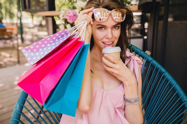 Портрет молодой улыбающейся счастливой красивой женщины с возбужденным выражением лица, сидящей в кафе с хозяйственными сумками, пьющими кофе, летний модный наряд, хипстерский стиль, розовое хлопковое платье, модная одежда
