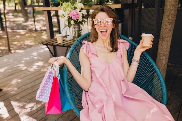 Портрет молодой улыбающейся счастливой симпатичной женщины с возбужденным выражением лица, сидящей в кафе с хозяйственными сумками, пьющими кофе, летней модной одежды, розового хлопкового платья, модной одежды