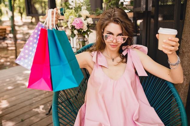 Портрет молодой улыбающейся счастливой красивой женщины с возбужденным выражением лица, сидящей в кафе с хозяйственными сумками, пьющими кофе, летний модный наряд, розовое хлопковое платье, модная одежда
