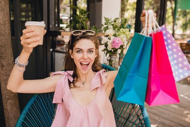 コーヒーを飲む買い物袋とカフェに座って興奮した表情で若い笑顔の幸せなきれいな女性の肖像画