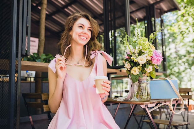 Портрет молодой улыбающейся счастливой симпатичной женщины с сидя в кафе, пьющей кофе, летний модный наряд, розовое платье из хлопка, модные аксессуары одежды