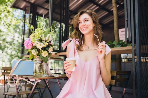 Портрет молодой улыбающейся счастливой красивой женщины с сидением в кафе, пить кофе