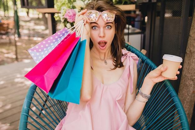 Портрет молодой улыбающейся счастливой симпатичной женщины с удивленным выражением лица, сидящей в кафе с хозяйственными сумками, пьющими кофе, летний модный наряд, розовое платье из хлопка, модная одежда