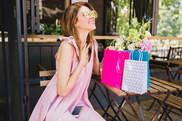 Портрет молодой улыбающейся счастливой симпатичной женщины с удивленным выражением лица, сидящей в кафе с хозяйственными сумками, летней модной одежды, розового хлопкового платья, модной одежды