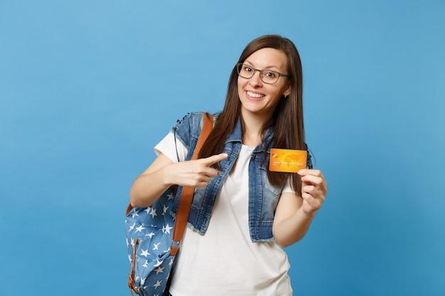 Портрет молодого улыбающегося симпатичного студента женщины в очках с рюкзаком, указывающим указательным пальцем на кредитной карте в руке, изолированной на синем фоне. образование в концепции колледжа университета средней школы.
