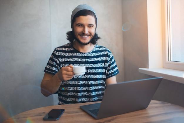 커피를 마시고 집에 일하는 젊은 웃는 남자의 초상화.