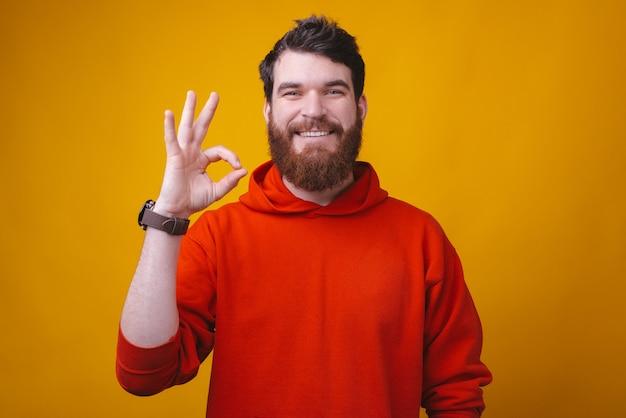 Портрет молодого улыбающегося человека, показывая хорошо жестом над желтой стеной, все в порядке