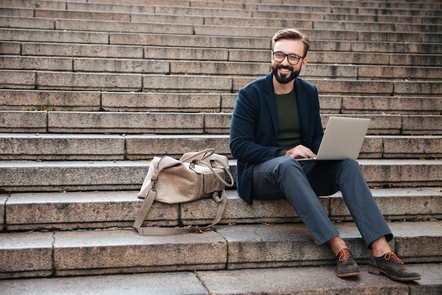 Портрет молодого улыбающегося человека с помощью портативного компьютера