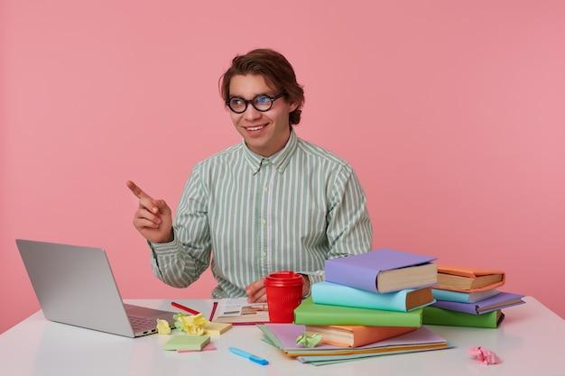 Портрет молодого улыбающегося человека в очках, сидящего за столом с книгами, работающего за ноутбуком, выглядит веселым, смотрит и указывает пальцами влево на розовом фоне.