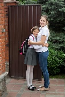 学校に娘を見送る若い笑顔の母親の肖像画