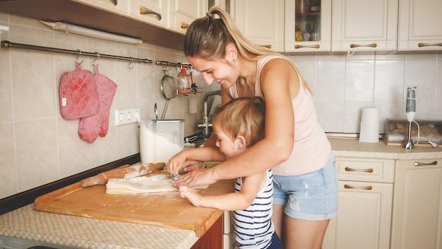 그녀의 3 세 유아 소년 베이킹과 부엌에서 쿠키 만들기를 가르치는 젊은 웃는 어머니의 초상화