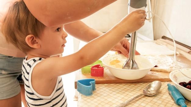 Портрет молодой улыбающейся матери учит своего 3-летнего мальчика выпекать и делать печенье на кухне